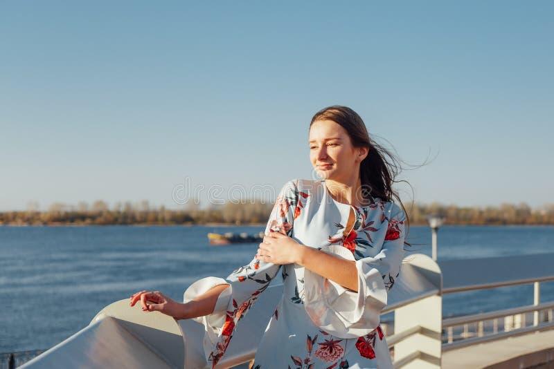Ung stilfull kvinna, i delikat bl?tt kl?nninganseende p? stranden och att tycka om solnedg?ngen royaltyfri foto
