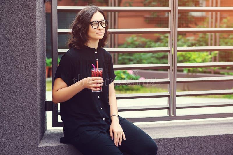 Ung stilfull kvinna i exponeringsglas med lemonad, utomhus Flicka i tillfällig kläder som rymmer sommarcoctailen på kaféterrassen royaltyfri fotografi