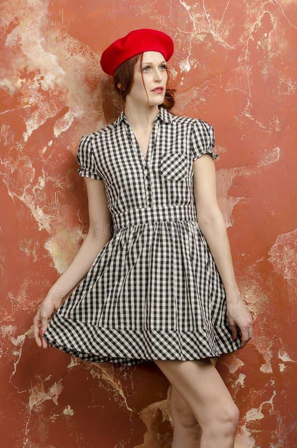 Ung stilfull kvinna i stilfull klänning i tappningstil och en röd basker fotografering för bildbyråer