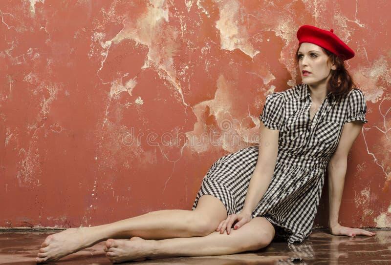 Ung stilfull kvinna i stilfull klänning i tappningstil och en röd basker royaltyfri fotografi