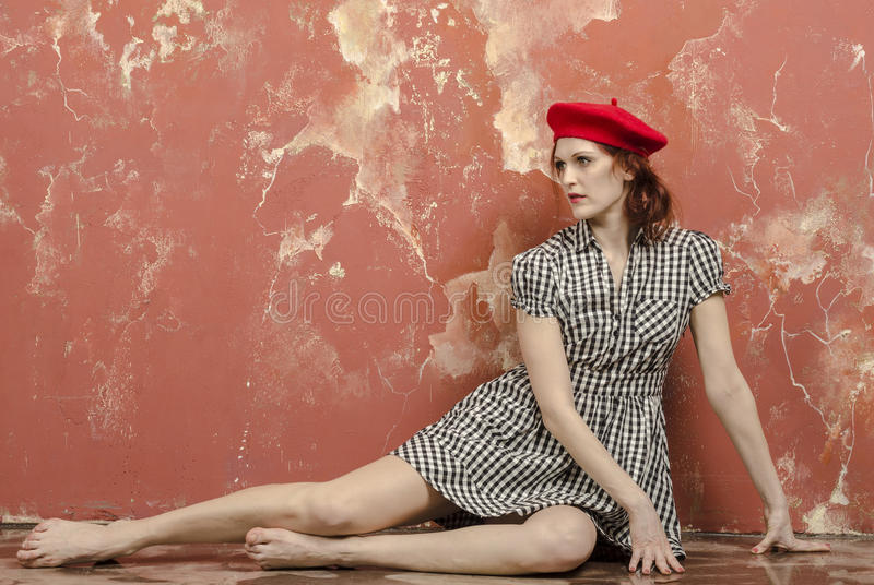 Ung stilfull kvinna i stilfull klänning i tappningstil och en röd basker arkivbild