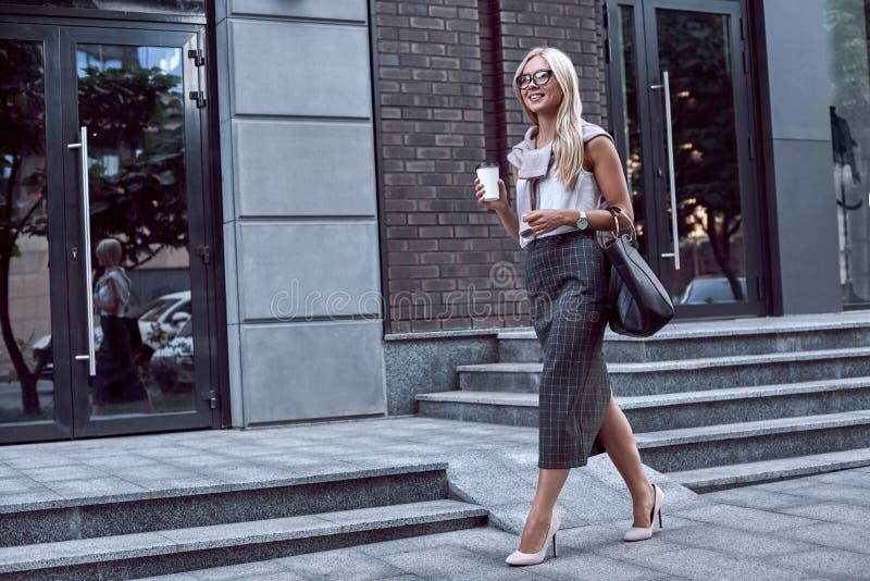 Ung stilfull kvinna som går på gatan av centret med leende royaltyfri fotografi