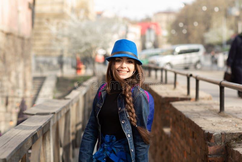 Ung stilfull kvinna som g?r p? den gamla stadgatan, lopp med ryggs?cken och den bl?a hatten 1990 byggde den lviv operatheatren uk fotografering för bildbyråer