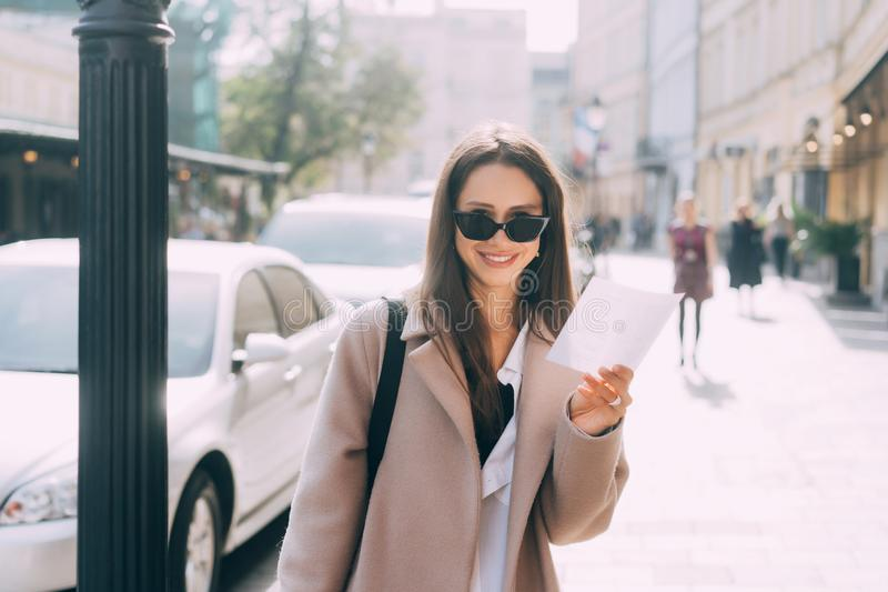 Ung stilfull kvinna som poserar på gatan och ser kameran royaltyfri bild