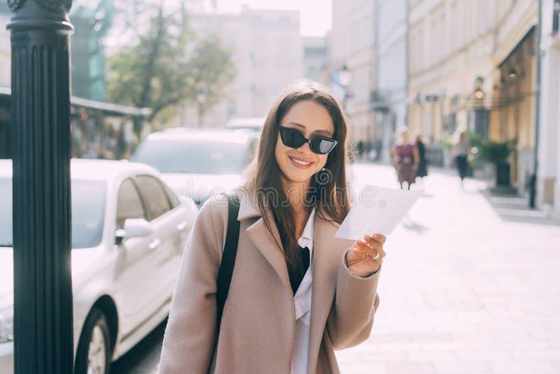 Ung stilfull kvinna som poserar på gatan och ser kameran arkivbild