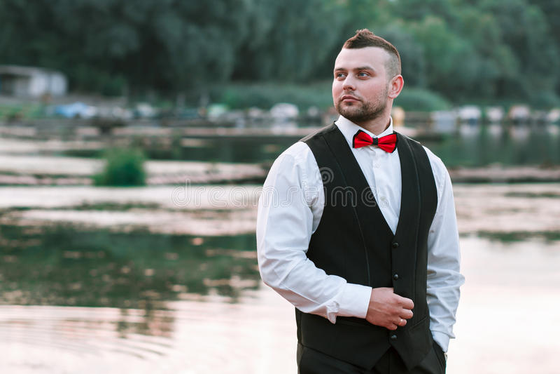 Ung stilfull man i en waistcoat, en horisontalstående av brudgummen, en stående på en bakgrund av naturen, floden och pir fotografering för bildbyråer