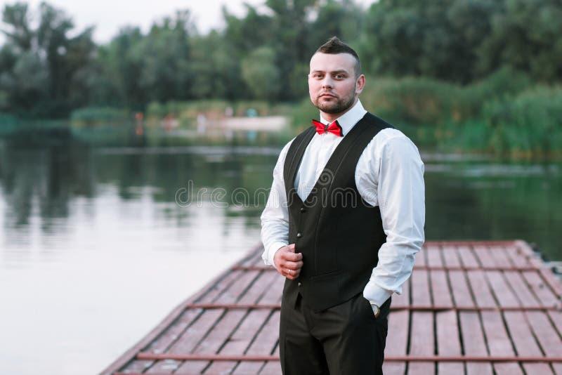 Ung stilfull man i en waistcoat, en horisontalstående av brudgummen, en stående på en bakgrund av naturen, floden och pir royaltyfri fotografi