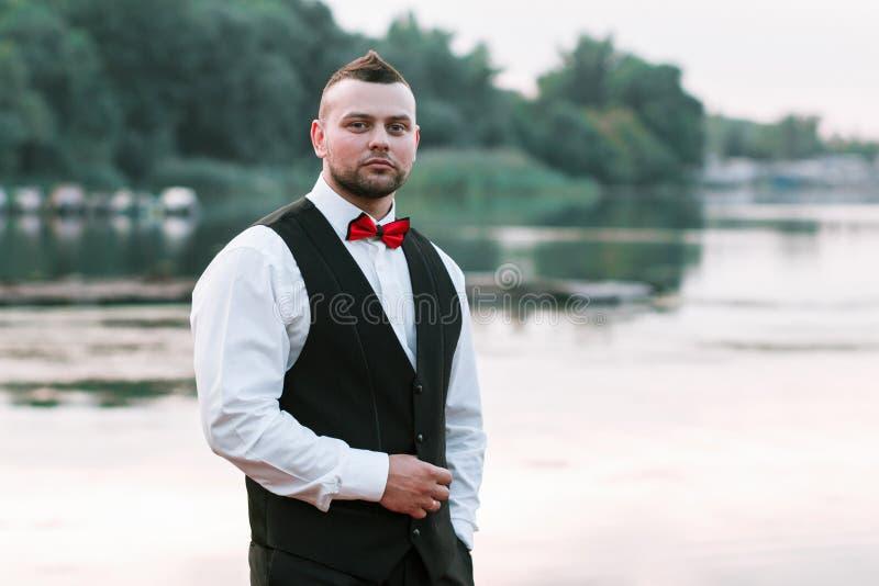 Ung stilfull man i en waistcoat, en horisontalstående av brudgummen, en stående på en bakgrund av naturen, floden och pir royaltyfri foto