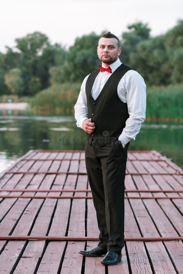 Ung stilfull man i en waistcoat, en vertikal stående av brudgummen, en stående på en bakgrund av naturen, floden och pir arkivfoton