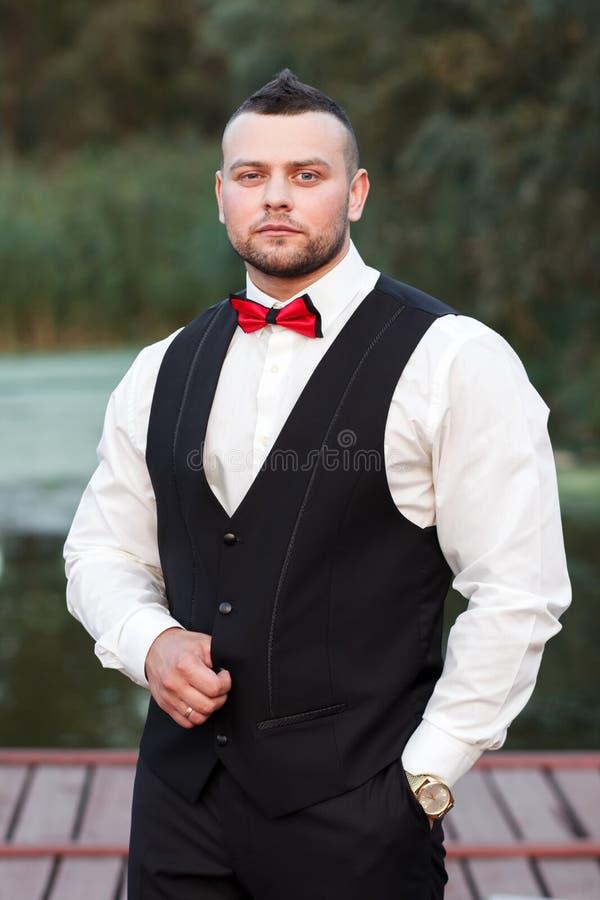 Ung stilfull man i en waistcoat, en vertikal stående av brudgummen, en stående på en bakgrund av naturen, floden och pir arkivbilder