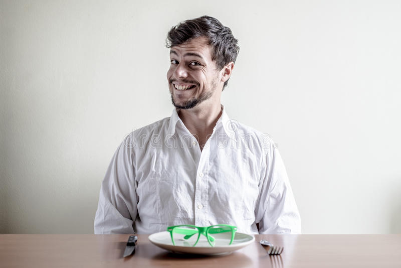 Ung stilfull man med den vita skjortan som äter grönt glasögon arkivfoto