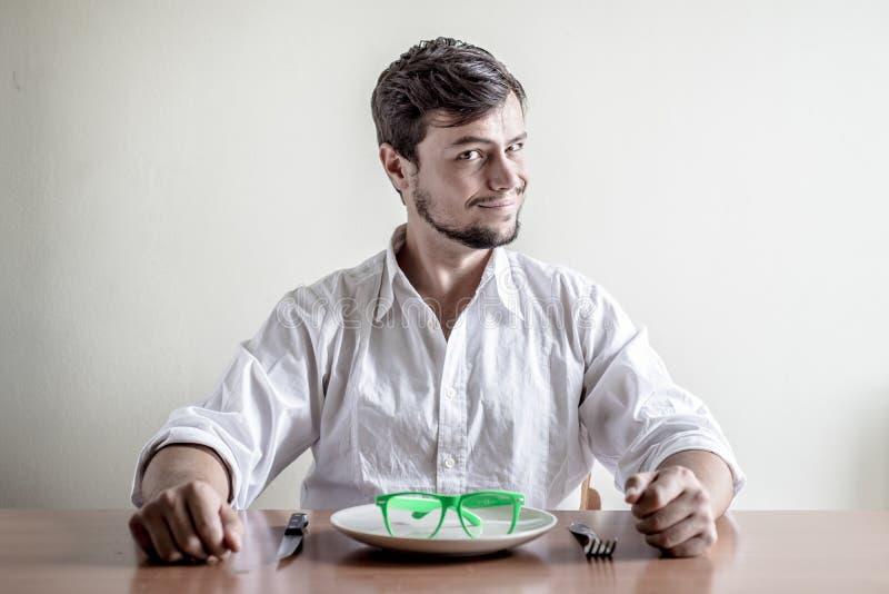 Ung stilfull man med den vita skjortan som äter grönt glasögon fotografering för bildbyråer
