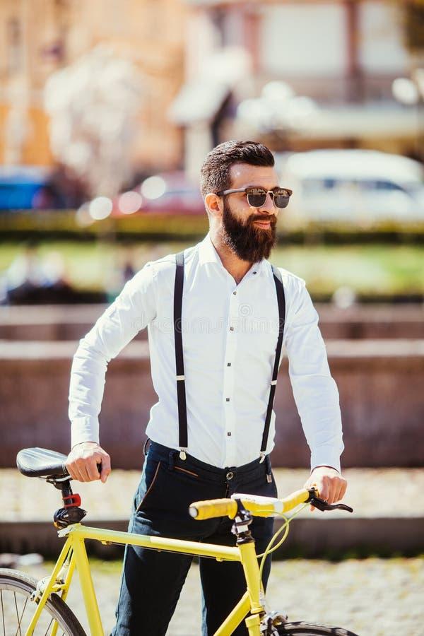 Ung stilfull man som går att arbeta med cykeln hipster med en fixiecykel på gatan skäggig man som ser bort, medan rida på hans arkivbilder