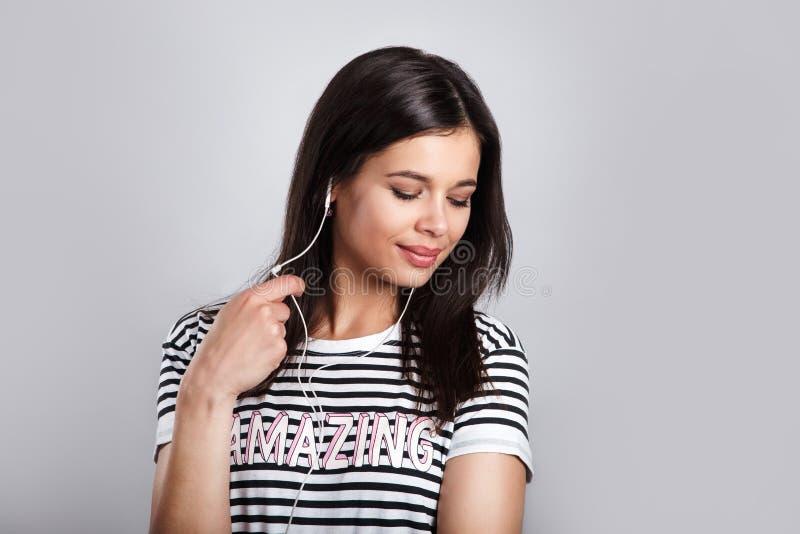 Ung stilfull nätt womant lyssnande musik med hörlurar och ilar telefonen arkivfoto