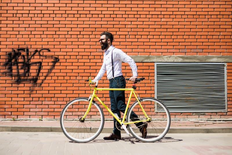 Ung stilfull skäggig man som går att arbeta med cykeln mot tegelstenväggen arkivfoto