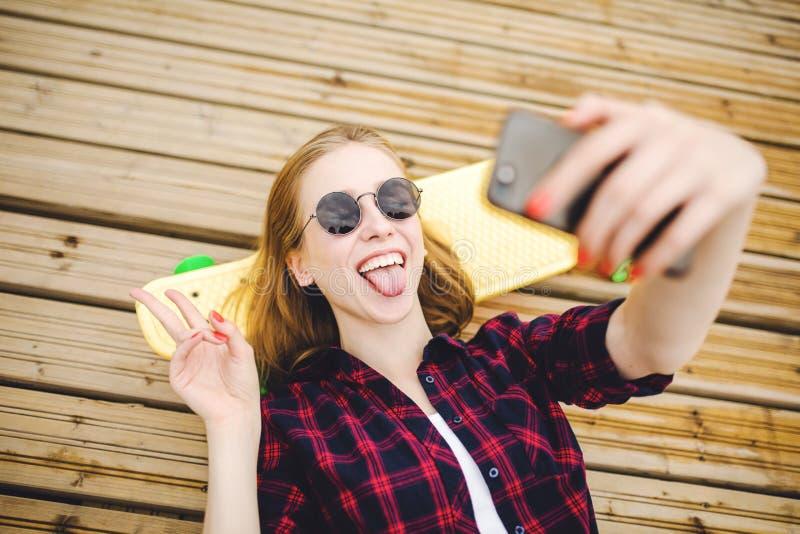 Ung stilfull stads- flicka i hipsterdräkten som gör selfie, medan ligga med på träpir royaltyfri foto