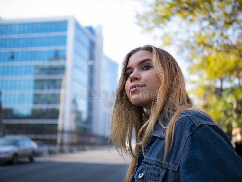 Ung stilfull tonåringflicka med flödande hår i ett grov bomullstvillomslag utomhus arkivfoton