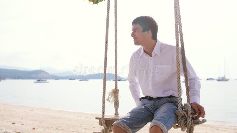 Ung stilig affärsman i den vita skjortan som svänger på hängmattan på den exotiska stranden royaltyfri bild