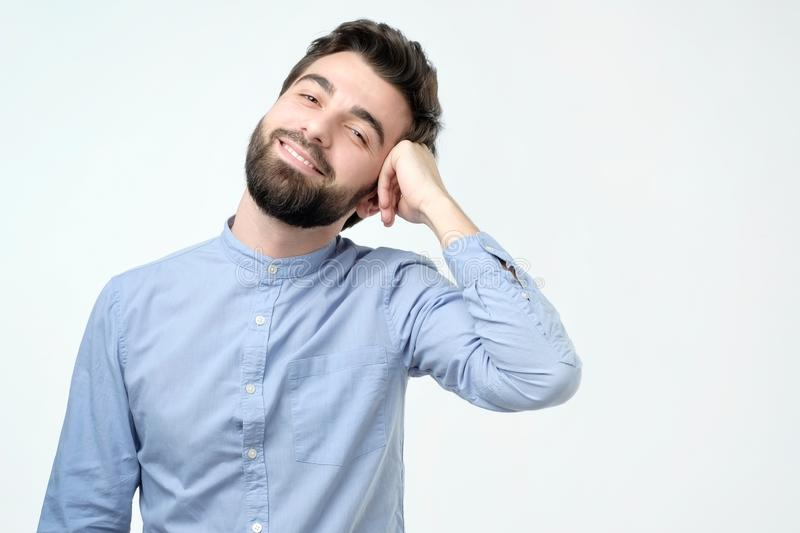 Ung stilig affärsman med den lyckliga framsidan som ler och ser kameran royaltyfria bilder