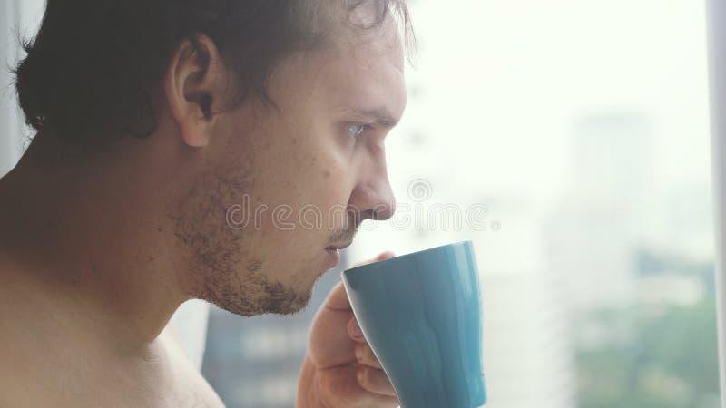 Ung stilig affärsman med ett skägg som dricker kaffe och ser stadstorn från ett fönster royaltyfri bild