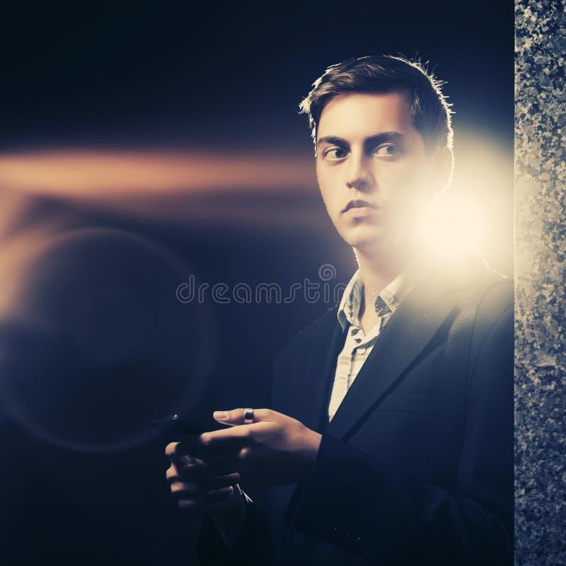 Ung stilig affärsman som använder smartphonen i en nattstadsgata royaltyfri fotografi