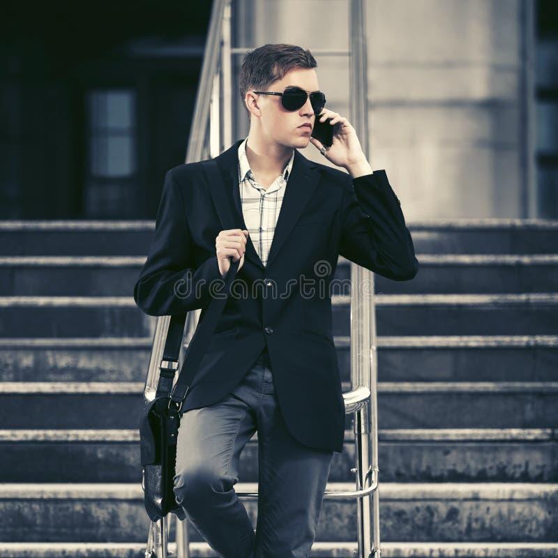 Ung stilig affärsman som kallar på mobiltelefonen i stadsgata royaltyfri bild