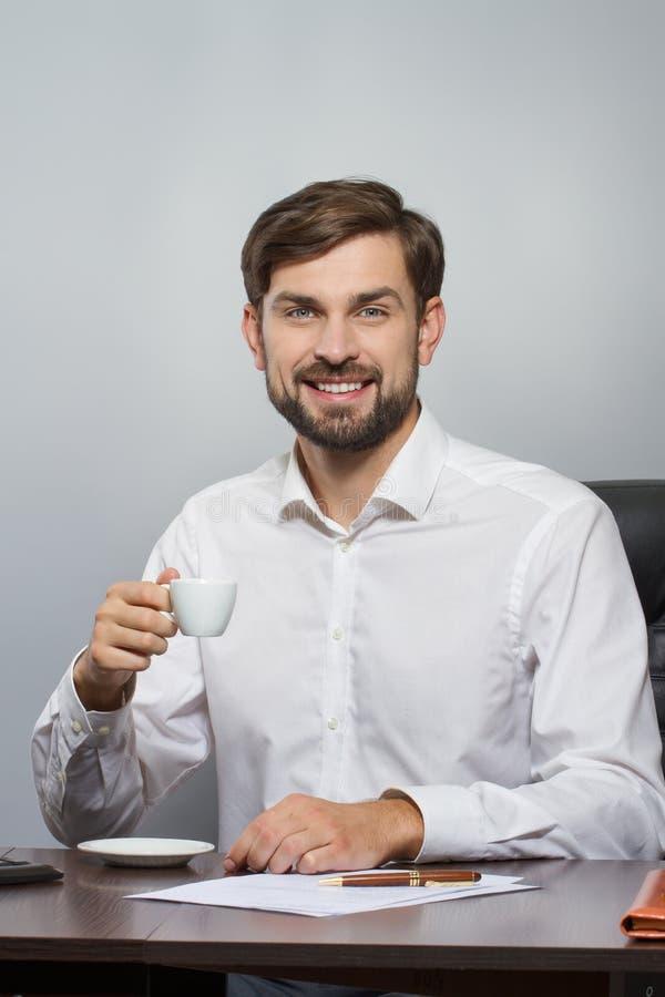 Ung stilig affärsman som ler med koppen kaffe arkivfoton