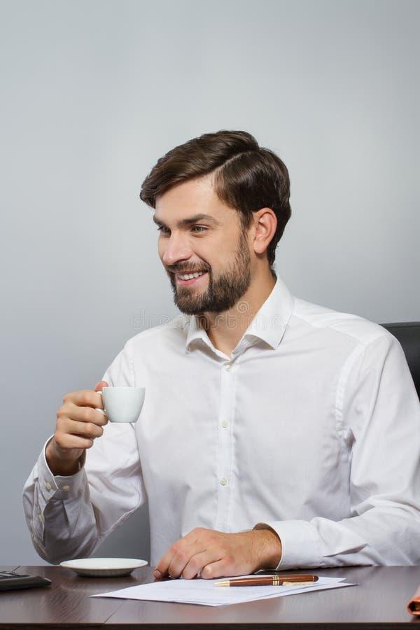 Ung stilig affärsman som ler med koppen kaffe arkivfoto