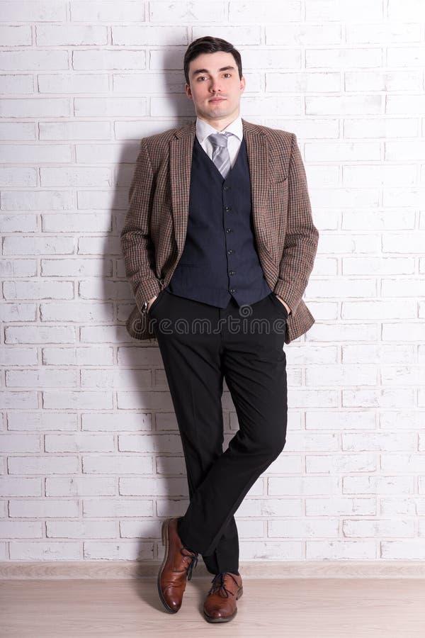 Ung stilig affärsman som poserar över den vita väggen royaltyfri foto