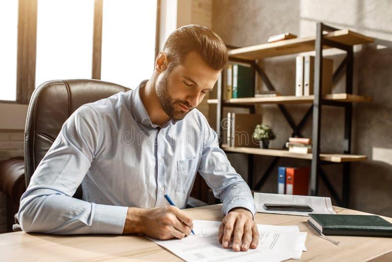 Ung stilig affärsman som sitter och skriver på tabellen i hans eget kontor Han satte häftet på dokument Worktime arkivbild