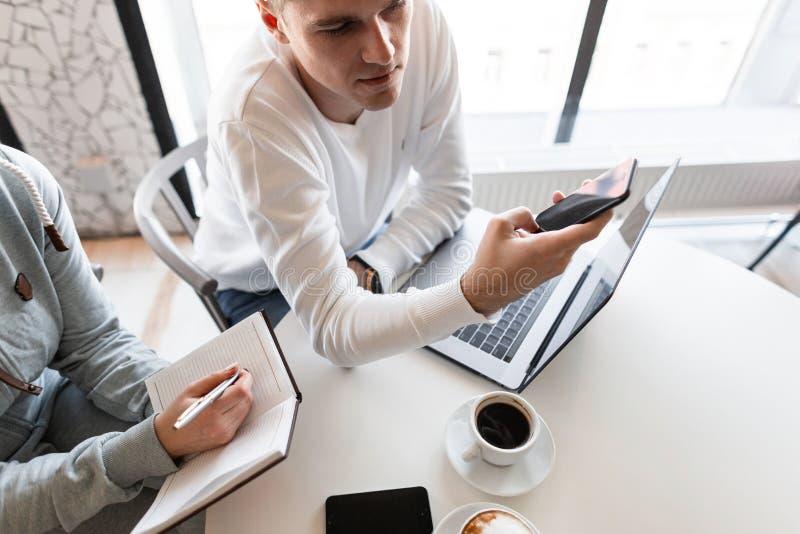 Ung stilig affärsman som sitter på tabellen i kontoret på ett affärsmöte med en kollega som använder en mobiltelefon arkivfoton