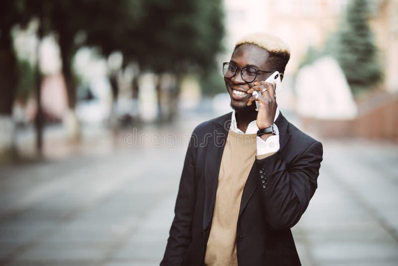 Ung stilig afro amerikansk affärsman som utomhus talar på hans mobiltelefon i gatan fotografering för bildbyråer