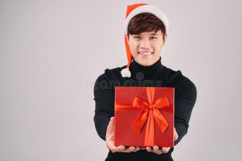 Ung stilig asiatisk man med den santa hatten som ger en röd gåva royaltyfria foton