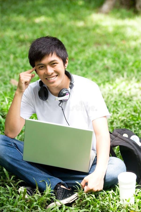 Ung stilig asiatisk student med bärbara datorn och leende i utomhus- royaltyfri bild