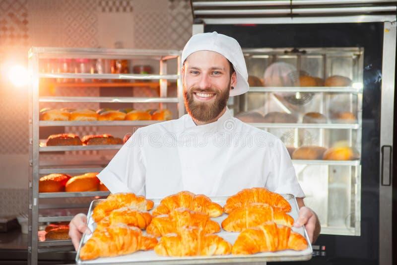 Ung stilig bagare som rymmer nytt bakade giffel i händer på bakgrunden av ugnen arkivfoto