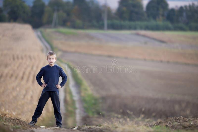 Ung stilig blond barnpojke som bara står på jordvägen amo royaltyfri bild