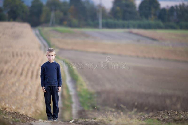 Ung stilig blond barnpojke som bara står på jordvägen bland guld- gräs- vetefält på suddiga dimmiga gröna träd och royaltyfri fotografi