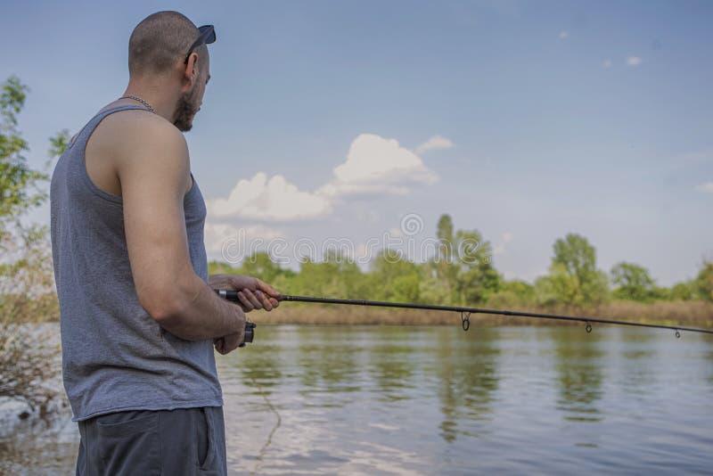 Ung stilig brutal caucasian man i tillfälligt dräktfiske på arkivbild