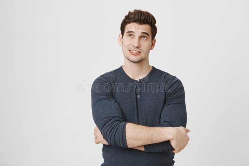 Ung stilig europeisk student med bruntögon och stilfull frisyr som står med korsade händer och ser upp arkivbild