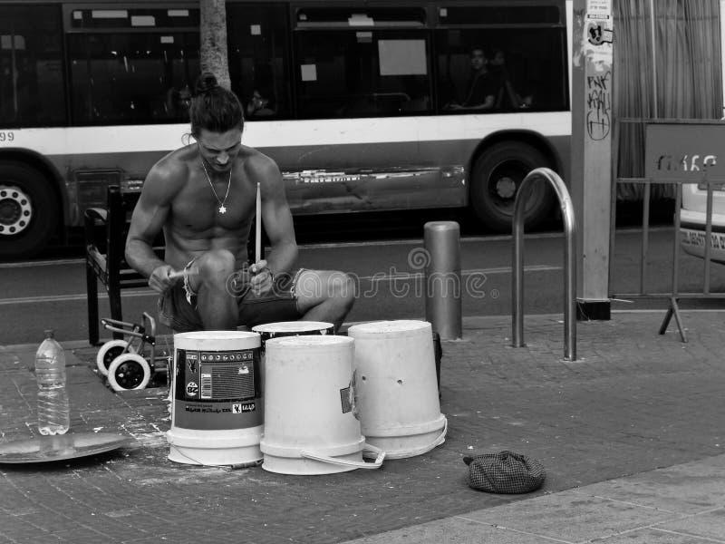 Ung stilig gatamusiker som spelar valsar på behållareaskar i en stads- inbrottframdel av en buss royaltyfria bilder