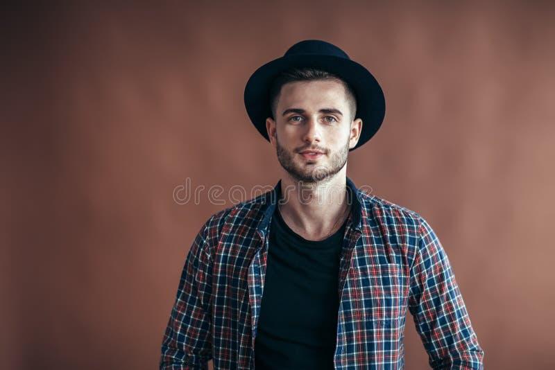 Ung stilig hipsterman i hatten som poserar på brun bakgrund royaltyfri fotografi