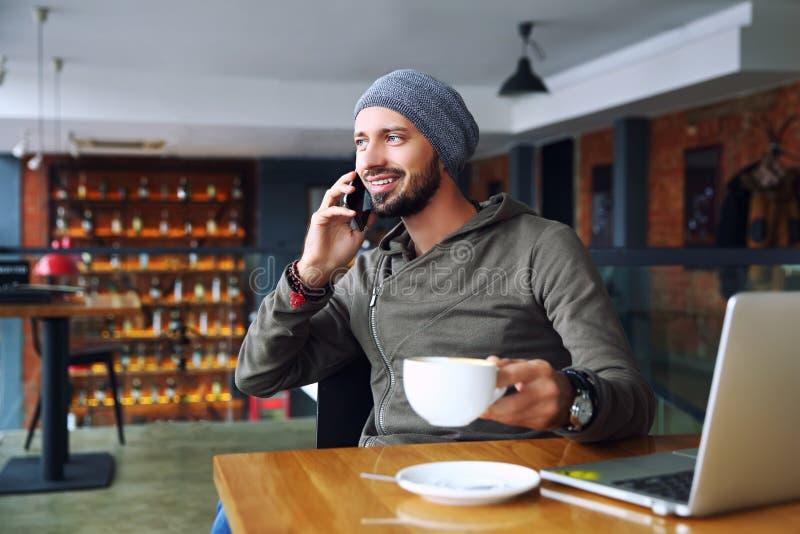 Ung stilig hipsterman med skäggsammanträde, i talande mobiltelefon för kafé, hållande kopp kaffe och att le Bärbar dator på arkivfoto