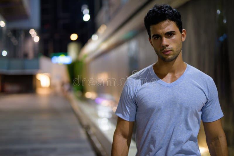 Ung stilig latinamerikansk man som undersöker stadsgatorna på natten royaltyfria foton