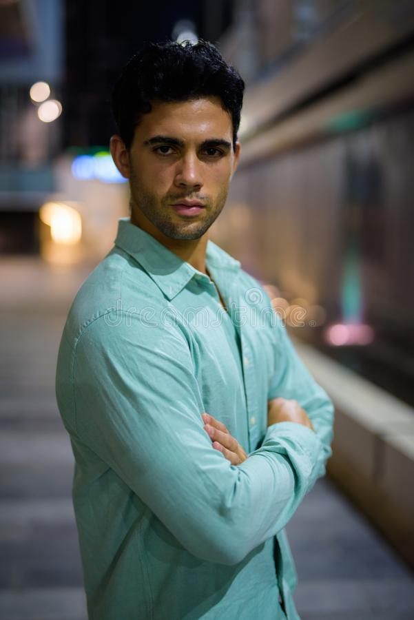 Ung stilig latinamerikansk man som undersöker stadsgatorna på natten arkivfoto