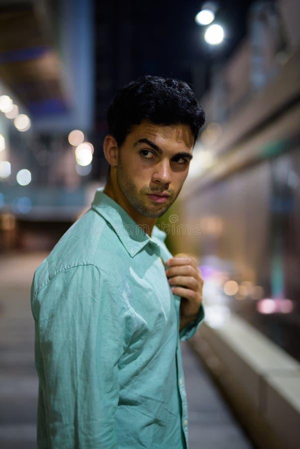 Ung stilig latinamerikansk man som undersöker stadsgatorna på natten arkivbilder