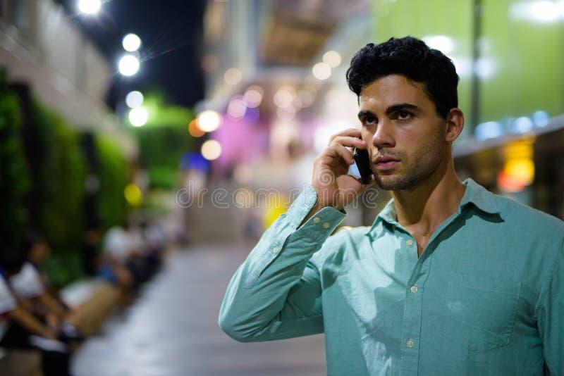 Ung stilig latinamerikansk man som undersöker stadsgatorna på natten arkivbild