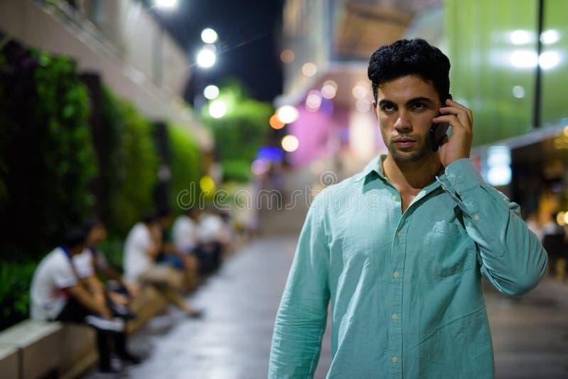 Ung stilig latinamerikansk man som undersöker stadsgatorna på natten royaltyfri foto