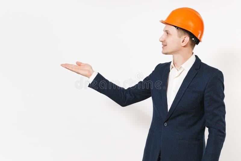 Ung stilig lyckad affärsman i den mörka dräkten, skyddande hardhat som åt sidan pekar handen på kopieringsutrymme som isoleras på fotografering för bildbyråer