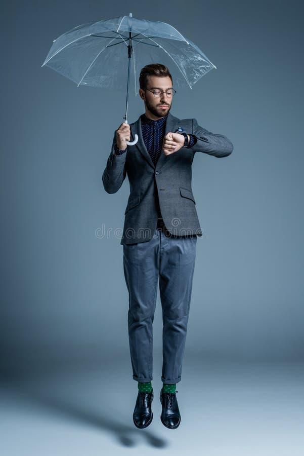 Ung stilig man i dräkt och exponeringsglas som rymmer ett paraply och se arkivbilder