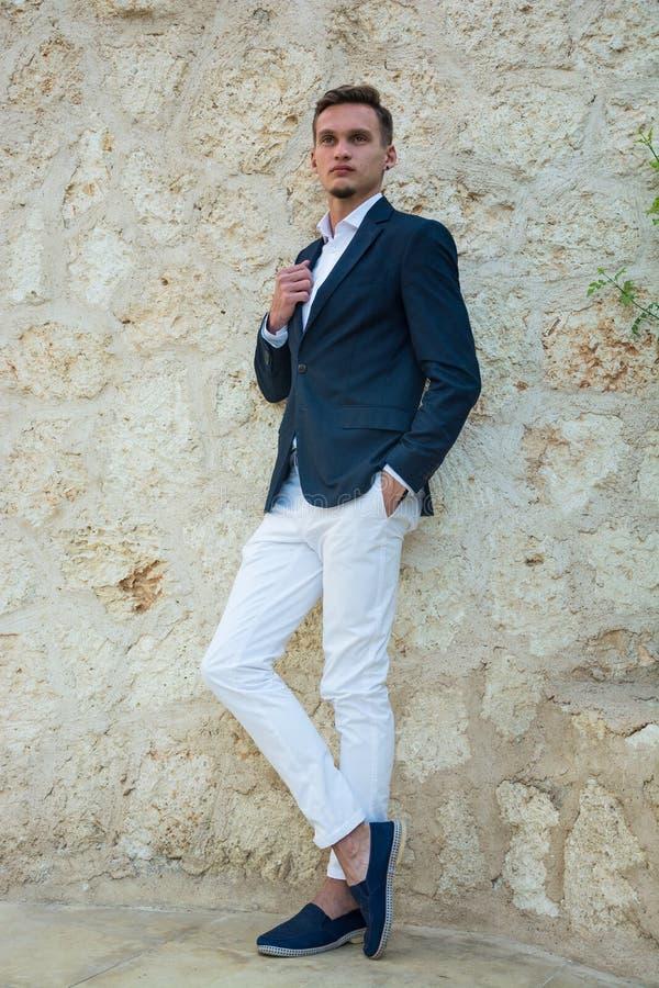 Ung stilig man i en dräkt och vit byxa på att stå nära en stenvägg arkivfoton